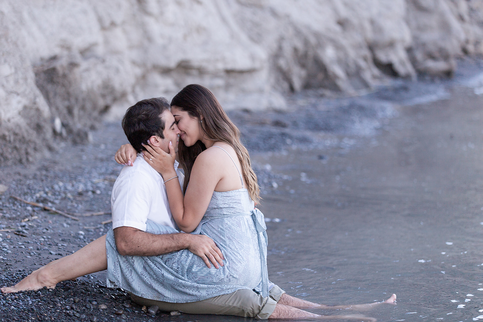 Toronto Man and Woman on Scarborough Bluffs Beach, Facing Eachother and Kissing - Engagement Session by Captured by Kirsten